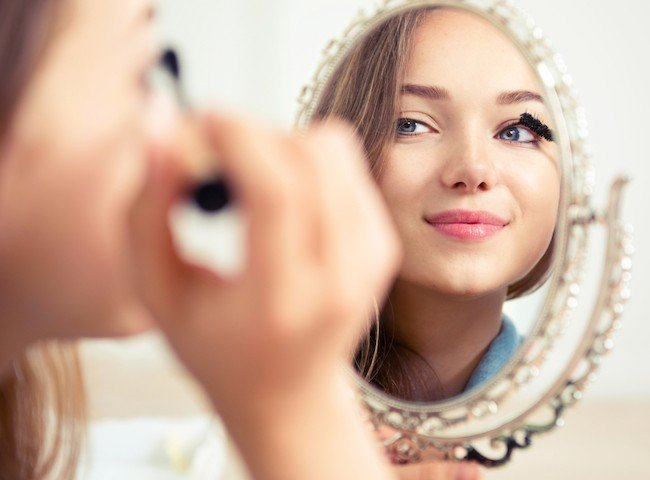 Beauty-model-teenage-girl-looking-in-the-mirror-and-applying-mascara-make-up.-Beautiful-young-woman-apply-makeup