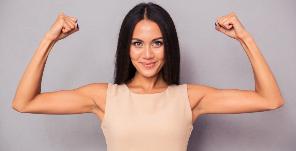 Happy elegant woman showing her biceps